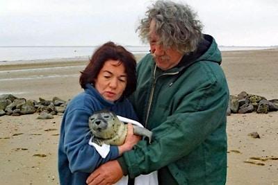Janine Bahr van Gemmert und André van Gemmert mit einem geretteten Heuler im Arm, Robbenzentrum Föhr.