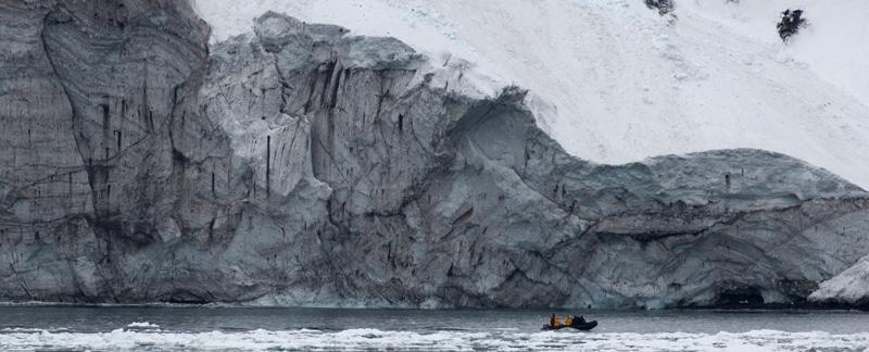Keine neuen Schutzgebiete in der Antarktis. Zodiac fährt an Eisbergkante vorbei.