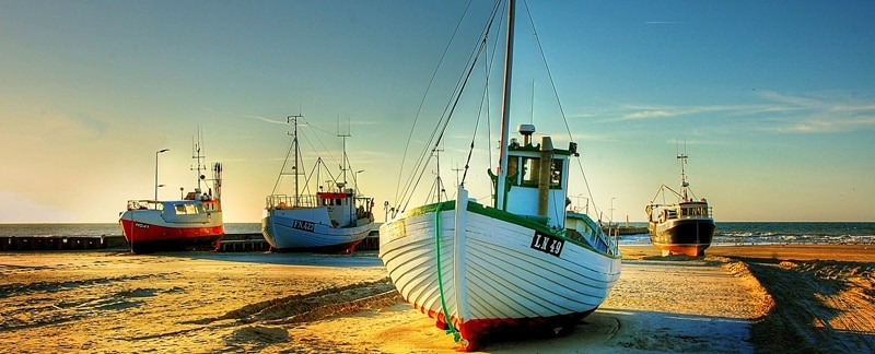 Vier kleine Fischkutter liegen bei Ebbe auf Sand.