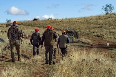 Mehrere Jäger gehen durch Graslandschaft.