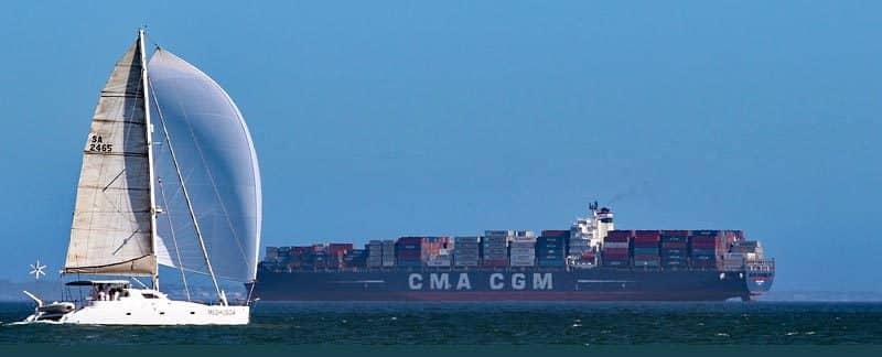 Ein Katamaran fährt vor einem Containerschiff.